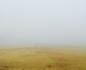 Foggy scene with brown grass and a small soccer goal.